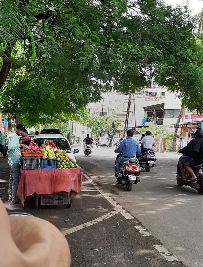 In this images the fruit sellar selling many types of fruits on the road of the corner and peoples are also in the pics  royalty free stock photos