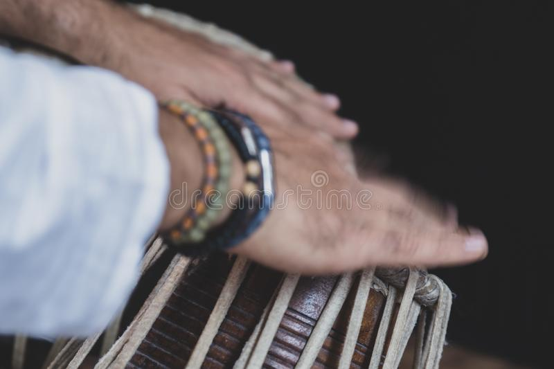 Images of a man`s hands wearing beads playing the Tabla. - royalty free stock photo