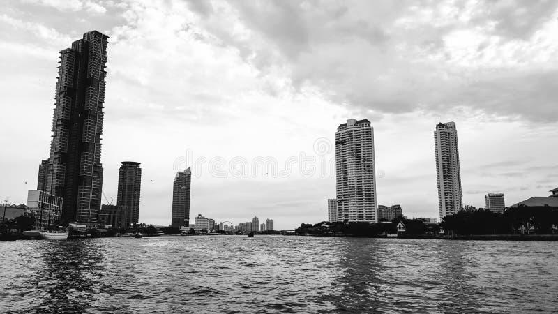 Images noires et blanches de la belle vue de Chao Phraya River parmi beaucoup d'édifices hauts le soir photos stock