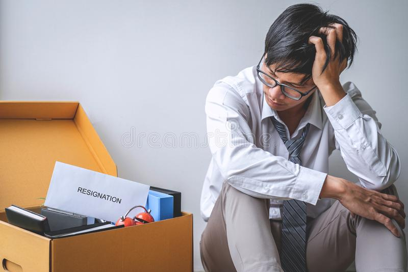 Images of packing up all his personal belongings and files into a brown cardboard box, Businessman has frustrated and stressed to stock photography