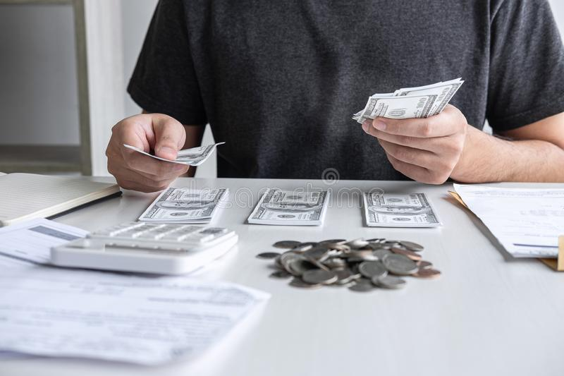 Images of stacking coin pile and Husband using calculator to calculating expenditure receipt bills of various activity cost and royalty free stock photography