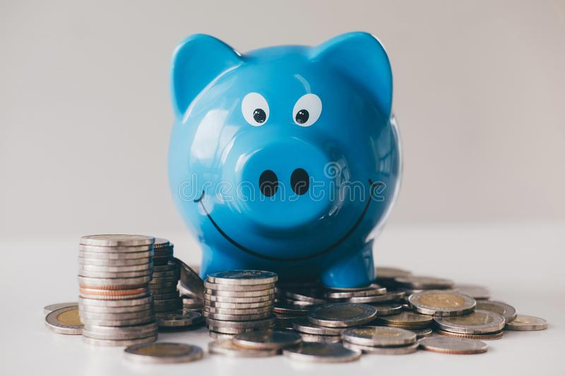 Images of stacking coins pile and blue smiling piggy bank to growing and savings with money box, Saving money for future plan and stock photography