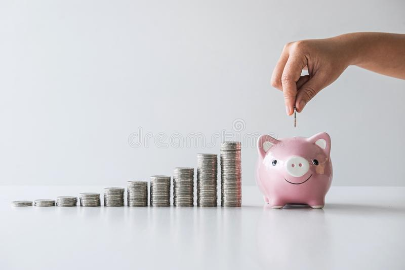 Images of stacking coins pile and Hand putting coin into pink piggy bank for planning step up to growing and savings with money royalty free stock photography