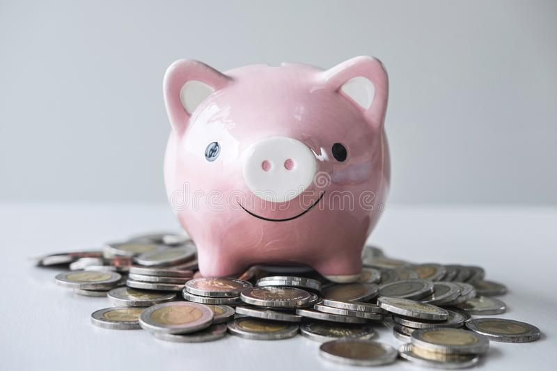 Images of stacking coins pile and pink smiling piggy bank to growing and savings with money box, Saving money for future plan and stock photos