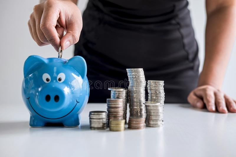 Images of stacking coins pile and woman hand putting coin into blue piggy bank for planning step up to growing and savings with royalty free stock photography