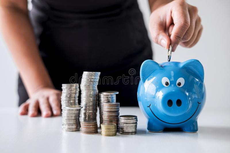 Images of stacking coins pile and woman hand putting coin into blue piggy bank for planning step up to growing and savings with stock image