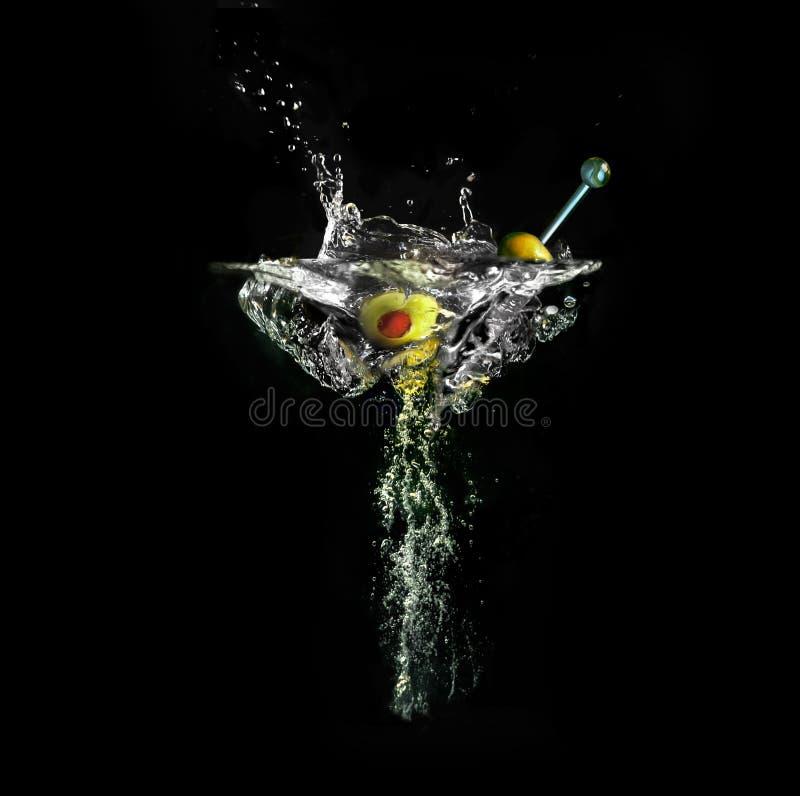 Imaginär vinglas med martini ut ur vattenfärgstänk och luftbubblor på svart bakgrund royaltyfria bilder
