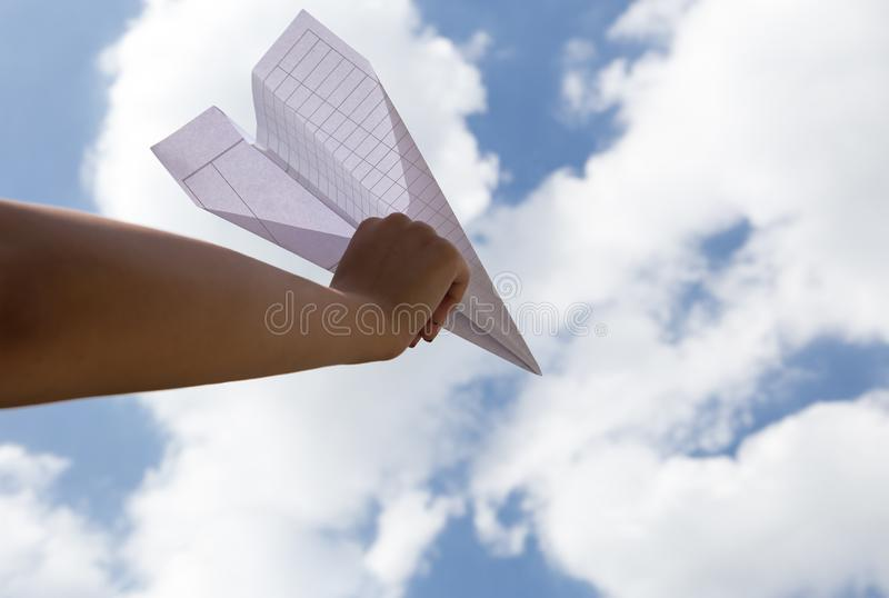 Imaginación del avión de papel que lanza de la mano de la mujer foto de archivo libre de regalías