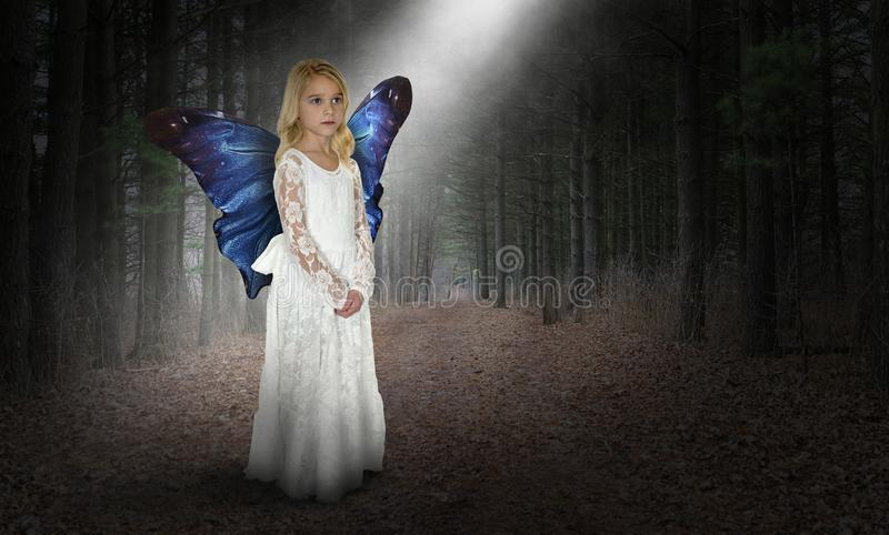 Imagination, Fantasy, Peace, Love, Nature, Hope, Spiritual Rebirth. A young girl uses her imagination to pretend she is an angel with fantasy butterfly wings in stock photography