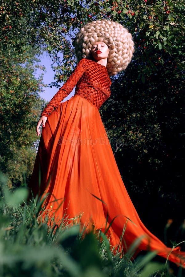 Imagination. Femme stylisée artistique dans la robe rouge à la mode et la grande perruque crépue photo stock