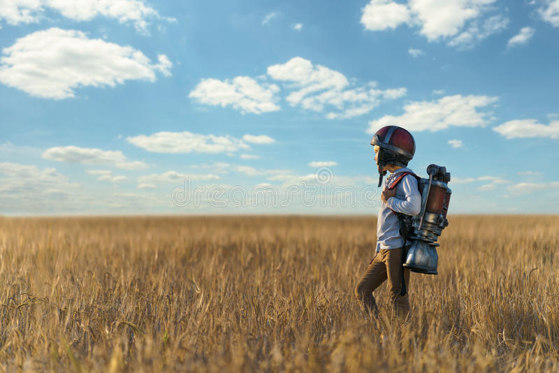 Imagination. Little boy in helmet in a field royalty free stock photography