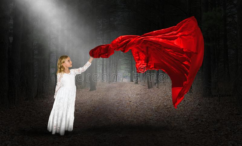 Imagination, Peace, Love, Nature, Wind, Surreal. A young girl plays with the wind and a red cloth fabric in this surreal abstract concept for peace, love, nature royalty free stock image