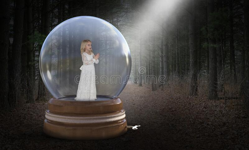 Imagination, Surreal, Nature, Hope, Love, Girl. A young girl is trapped in a snow globe in a deep, dark, mysterious forest or woods. Surreal abstract concept for royalty free stock images