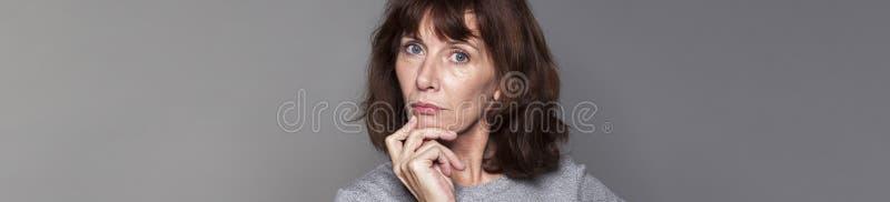 Imaginative beautiful 50s woman looking serious stock photos