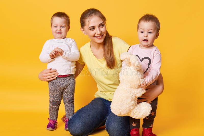 Imagine of young beautiful mother with little twin girls posing isolated over yellow background, children wants to play with their royalty free stock photography