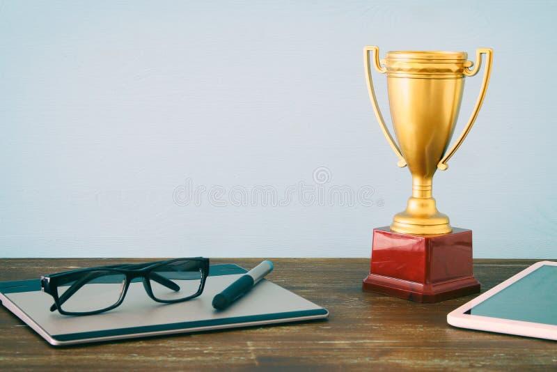 Imago de la visión superior de la tabla de la oficina con el trofeo de oro de los artículos digitales Concepto de la excelencia d fotografía de archivo libre de regalías