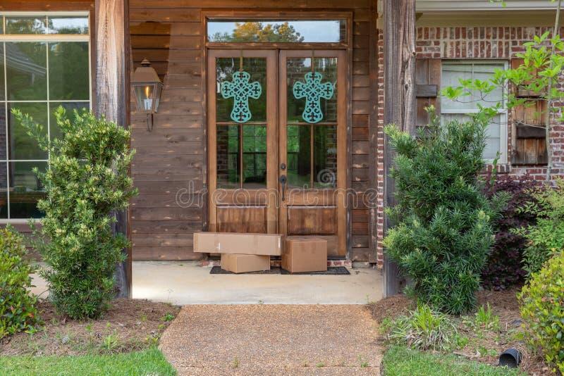 Imballaggi di spedizione sul portico anteriore della casa, davanti alla porta fotografia stock