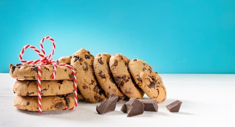 Imballaggio dei biscotti al cioccolato su tavoletta di legno bianca e sfondo blu Copia spazio fotografia stock