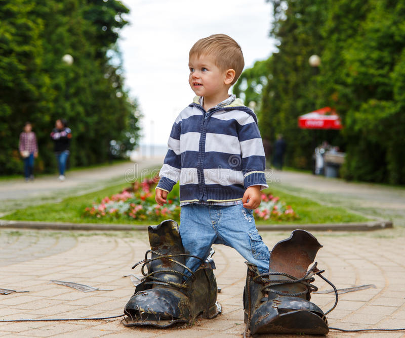 Imbarazzato due anni del ragazzo che sta negli stivali giganti immagini stock