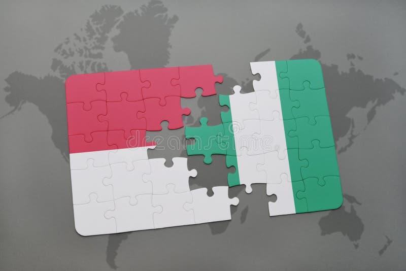 Imbarazzi con la bandiera nazionale dell'Indonesia e della Nigeria su un fondo della mappa di mondo illustrazione vettoriale