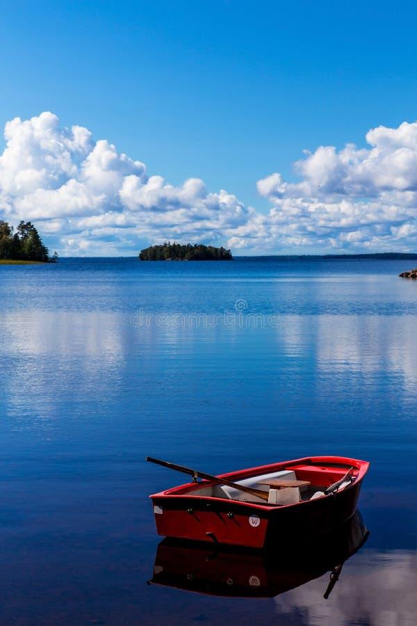 Imbarcazione a remi rossa sopra alla baia idilliaca fotografia stock