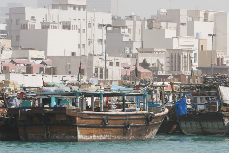 Imbarcazioni a vela di legno dei Dhows del Dubai UAE le vecchie sono messe in bacino lungo il lato di Deira di Dubai Creek. immagine stock
