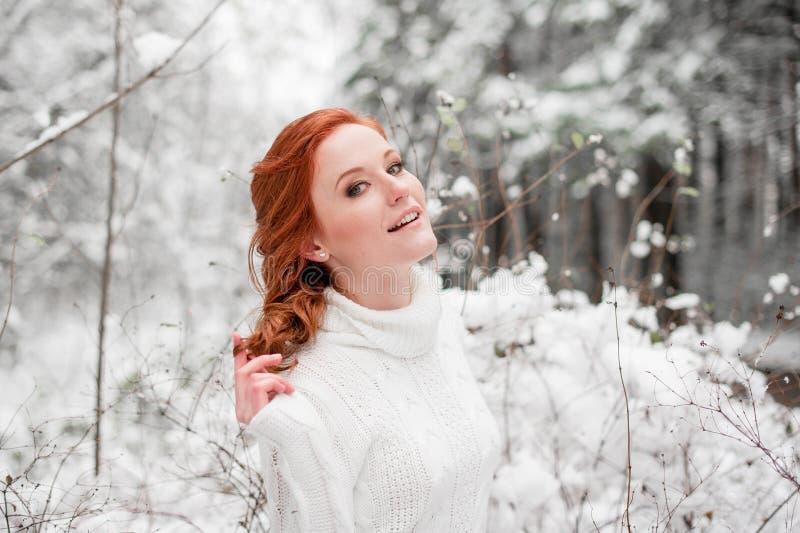 Imbirowa atrakcyjna kobieta w białym pulowerze w zimie lasowy Śnieżny Grudzień w parku Portret Bożenarodzeniowy śliczny czas obrazy stock