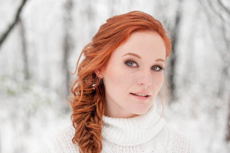 Imbirowa caucasian dziewczyna w białym pulowerze w zimie lasowy Śnieżny Grudzień w parku Portret Bożenarodzeniowy śliczny czas zdjęcia stock