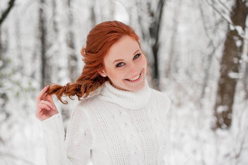 Imbirowa dziewczyna w białym pulowerze w zimie lasowy Śnieżny Grudzień w parku Święta tła blisko czerwony czasu obrazy stock