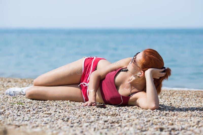 Imbirowa dziewczyna w sportswear i okularach przeciwsłonecznych kłama na otoczak plaży fotografia stock
