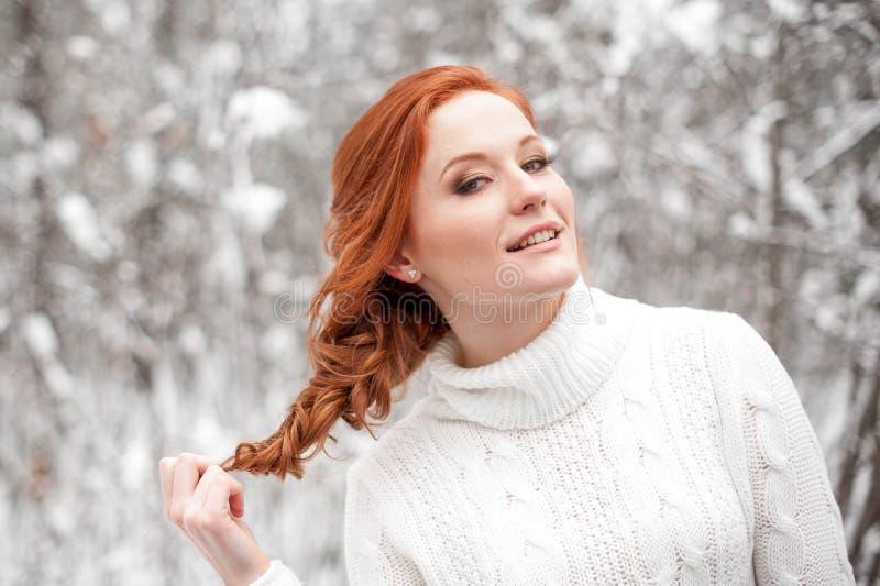 Imbirowa europejska dziewczyna w białym pulowerze w zimie lasowy Śnieżny Grudzień w parku Święta tła blisko czerwony czasu zdjęcie royalty free