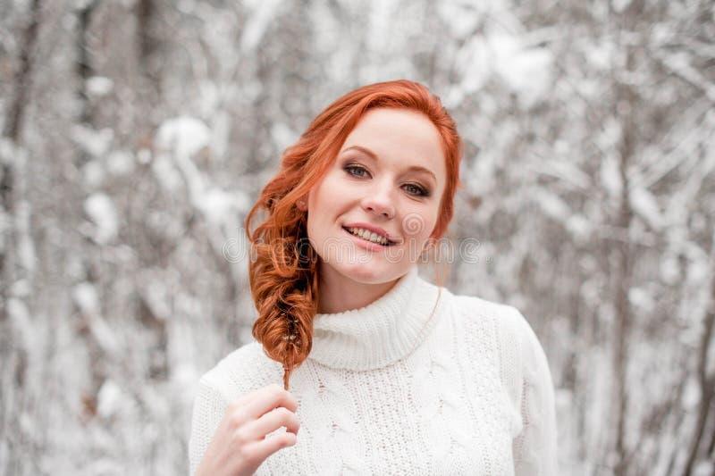 Imbirowa europejska dziewczyna w białym pulowerze w zimie lasowy Śnieżny Grudzień w parku Bożenarodzeniowy cudowny czas obrazy stock