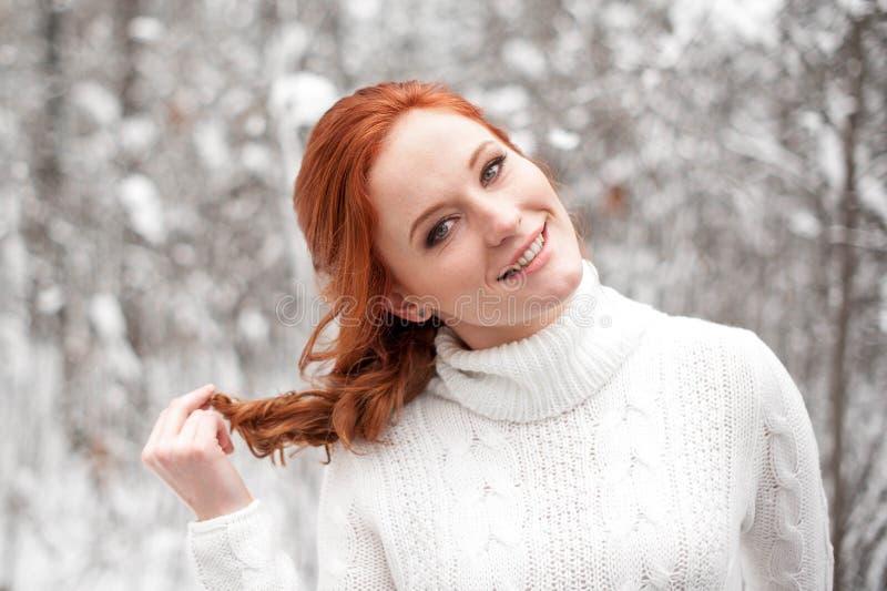 Imbirowa europejska dziewczyna w białym pulowerze w zimie lasowy Śnieżny Grudzień w parku Bożenarodzeniowy magiczny czas zdjęcie royalty free