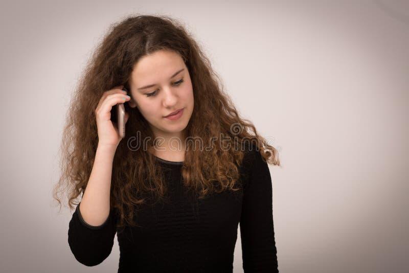 Imbirowa kobieta Opowiada Na Jej telefonie zdjęcie stock