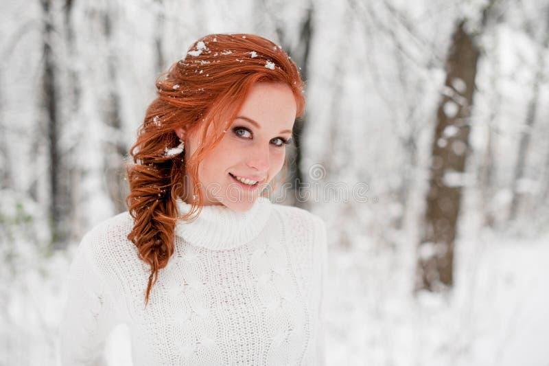 Imbirowa szczęśliwa kobieta w białym pulowerze w zimie lasowy Śnieżny Grudzień w parku Portret Bożenarodzeniowy śliczny czas zdjęcie royalty free