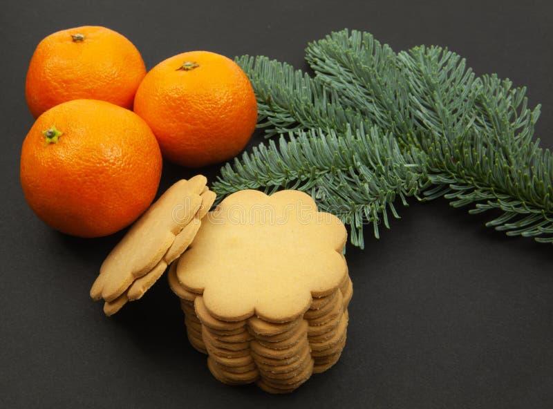 Imbirowi ciastka, jodeł gałąź i tangerines, na ciemnym tle obraz stock