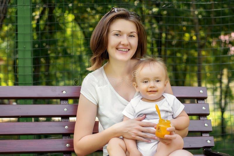Imbissbruch im Freien: gl?ckliche Mutter und wenig S?uglingskind, die auf Bank im Park sitzt Gesicht des Kindes ist befleckt mit  lizenzfreie stockbilder