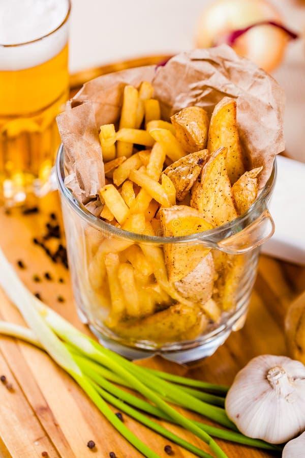 Imbisse für Bier Gebratene Kartoffeln in dienendem Glas auf hölzernem Brett lizenzfreies stockbild
