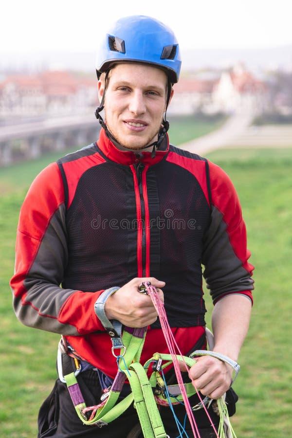 Imbracature giovani e sorrisi del paracadute della tenuta del paracadutista immagine stock libera da diritti