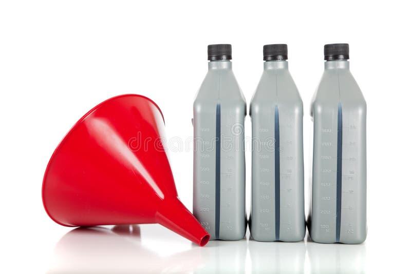 Imbuto rosso e quarti dell'olio di motore su bianco fotografia stock