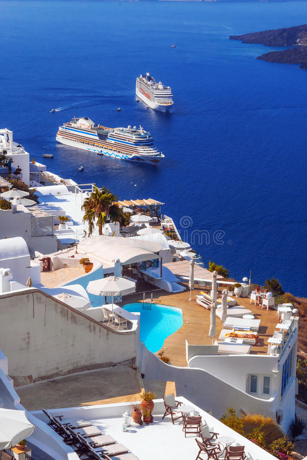 Imerovigli village architecture overlooking the cruise ships in the caldera, Santorini island royalty free stock images
