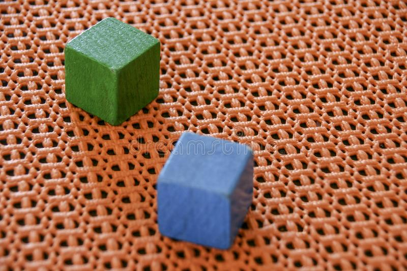 Two wooden toy cubes on an orange plastic  background. royalty free stock image