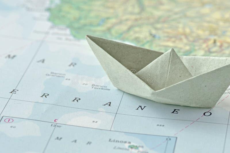 A imigração e pede o conceito do asilo - barco de papel no mapa fotos de stock