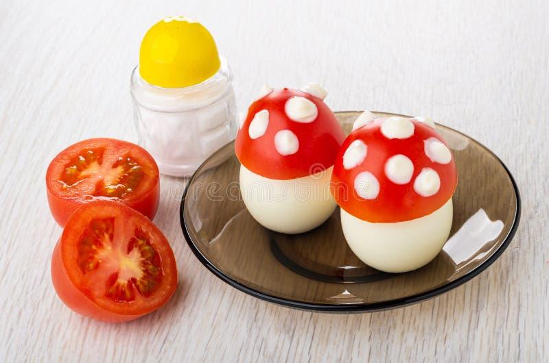 Imitación de la seta de los huevos con el tomate, mayonesa en el platillo, mitades del tomate, sal en la tabla de madera foto de archivo