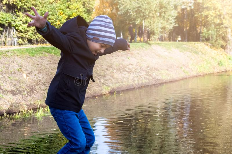 Imitatie van een sprong in de rivier door een kind in het Park in de herfst wordt uitgevoerd dat stock afbeeldingen