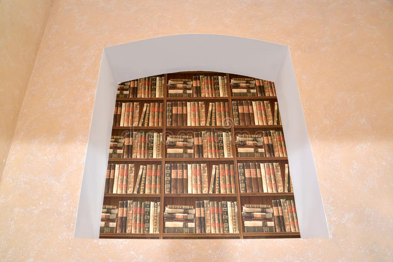 Imitation of a book rack in a niche. Interior fragment.  royalty free stock photos