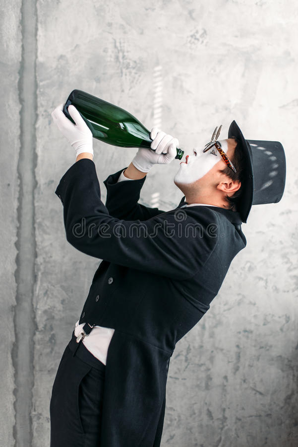 Imite al actor que bebe de una botella grande imagen de archivo