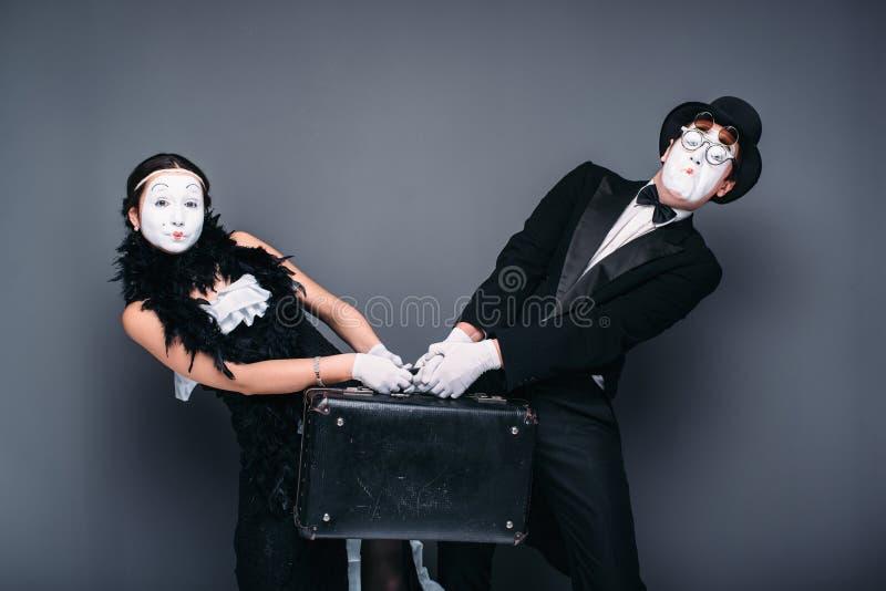 Imite el actor y a la actriz que se realizan con la maleta foto de archivo libre de regalías