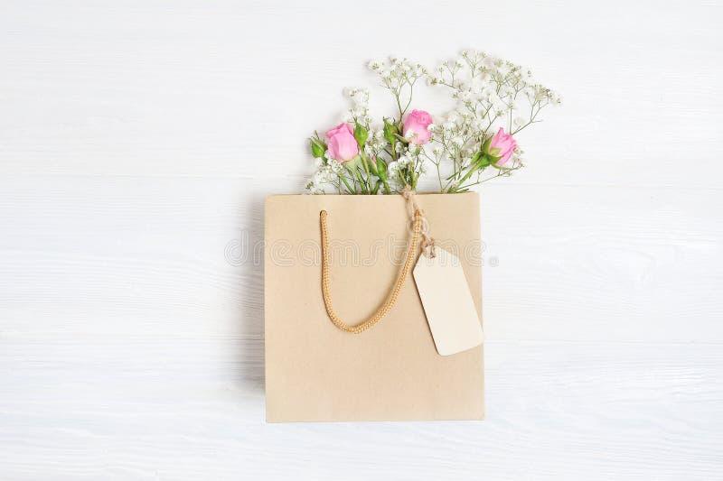 Imite encima de bolsa de papel de la composición y de la etiqueta del estilo rústico de las flores blancas, para el día del ` s d imagenes de archivo