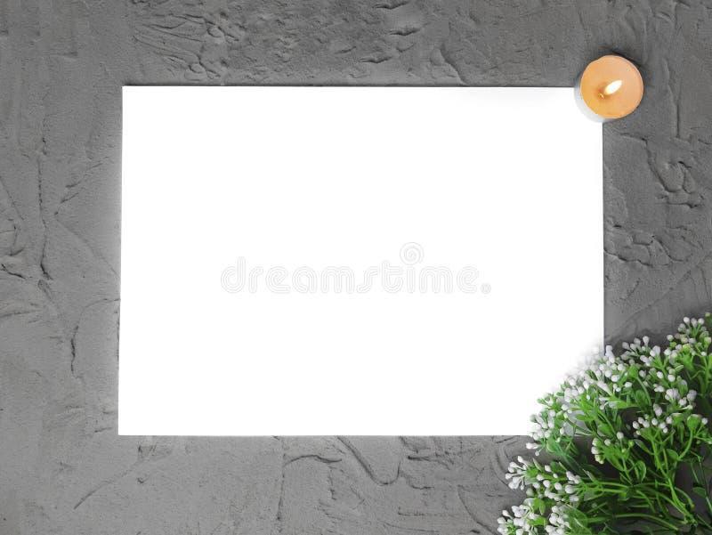 Imite encima de espacio en blanco vacío con la rama de las flores, quemando la vela en fondo gris fotos de archivo